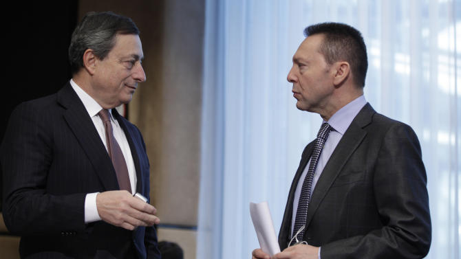 European Central Bank President Mario Draghi, left, speaks with Greek Finance Minister Yannis Stournaras during a meeting of the Macroeconomic Dialogue Group prior to a meeting of the eurogroup ministers in Brussels on Monday, March 4, 2013. The eurogroup finance ministers are set to discuss details of a bailout for cash-strapped Cyprus, further steps of assistance for Portugal and Ireland as well as the controversial issue of direct banking recapitalizations through Europe's permanent rescue fund. (AP Photo/Virginia Mayo)