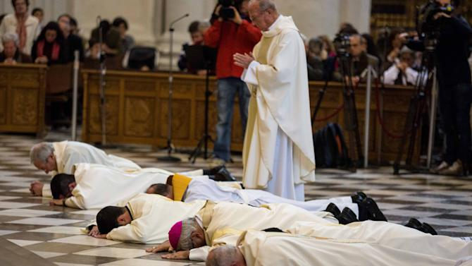 Archbishop of Granada Francisco Javier Martinez (3rdR) prostrates himself on the floor with other clergy at the city's cathedral in a gesture of apology to victims of abuse, November 23, 2014