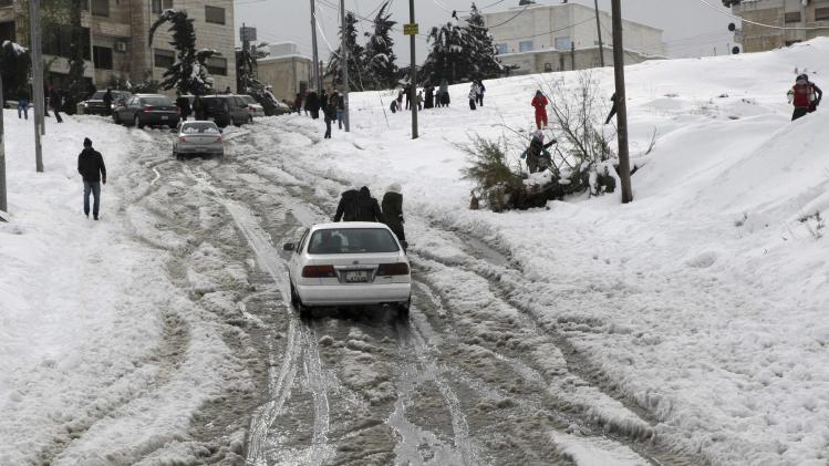 People play with snow after a heavy snowstorm in Amman