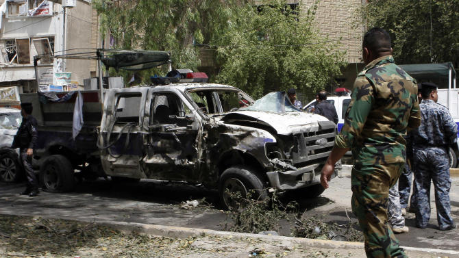 Security forces inspect the scene of a car bomb attack in the commercial area of Karradah in Baghdad, Iraq, Thursday, May 30, 2013. Iraqi officials say a series of morning bomb explosions in Iraq killed dozens in the latest eruption of violence rattling the country. (AP Photo/ Hadi Mizban)
