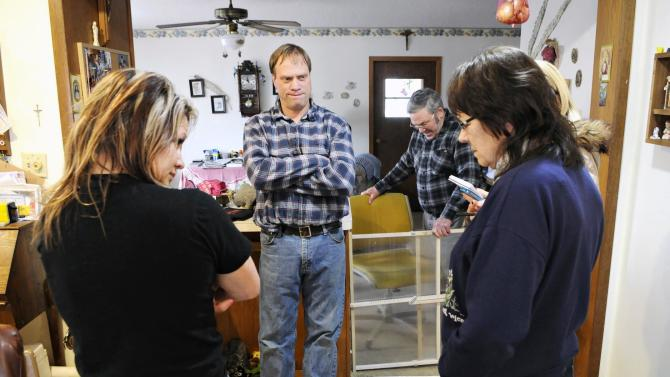 Cold Spring, Minn., Police Officer Tom Decker's sister Shelly, brother Eddie, father John and mother Rosella remember their brother and son in the kitchen of their family farm near Cold Spring Friday, Nov. 30, 2012. Decker was killed while on duty while doing a welfare check. (AP Photo/St. Cloud Times, Jason Wachter) NO SALES