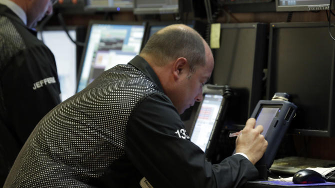 Trader Christopher Morie works on his handheld device on the floor of the New York Stock Exchange Monday, April 29, 2013. World stock markets were muted Tuesday May 7, 2013 as cheer over the better-than-expected U.S. jobs report faded. (AP Photo/Richard Drew)
