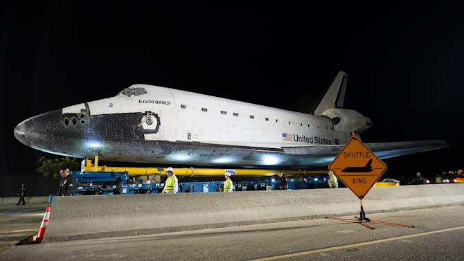 In this image provided by NASA the space shuttle Endeavour is seen atop the Over Land Transporter vehicle after exiting the Los Angeles International Airport on its way to its new home at the California Science Center in Los Angeles, Friday, Oct. 12, 2012.  Endeavour, built as a replacement for space shuttle Challenger, completed 25 missions, spent 299 days in orbit, and orbited Earth 4,671 times while traveling 122,883,151 miles. Beginning Oct. 30, the shuttle will be on display in the CSC's Samuel Oschin Space Shuttle Endeavour Display Pavilion, embarking on its new mission to commemorate past achievements in space and educate and inspire future generations of explorers. (AP Photo/Bill Ingalls, NASA) Photo Credit: NASA/Bill Ingalls