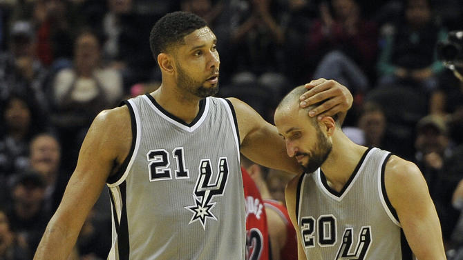 San Antonio Spurs forward Tim Duncan, left, congratulates Spurs guard Manu Ginobili, of Argentina, on a basket in the second half of an NBA basketball game, Friday, Dec. 19, 2014, in San Antonio. (AP Photo/Darren Abate)