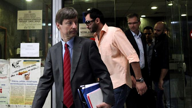 European Commission official Matthias Mors, left, and  Klaus Masuch of the European Central Bank, third left, leave the Labour Ministry after a meeting in Athens, Friday, July 6, 2012. The trio of International debt inspectors representing the IMF, ECB and the European Commission met Friday with Greek Labor Minister Andreas Likouretzos. (AP Photo/Petros Giannakouris)