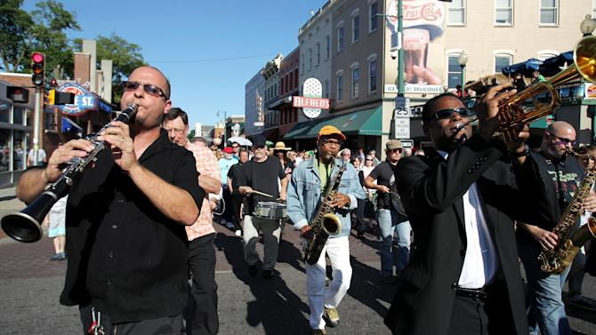 """Tom Link, from left, Kirk Whalum and Philip Joyner Jr. perform in a processional down Beale Street in Memphis, Tenn., Wednesday May 23, 2012,  to honor and celebrate Stax great Donald """"Duck"""" Dunn. Dunn, best known as the bass player for Booker T. & the MG's that helped define the Stax sound, was laid to rest Wednesday after passing away May 13 while on tour in Tokyo at age 70. (AP Photo/The Commercial Appeal, Mike Brown)"""