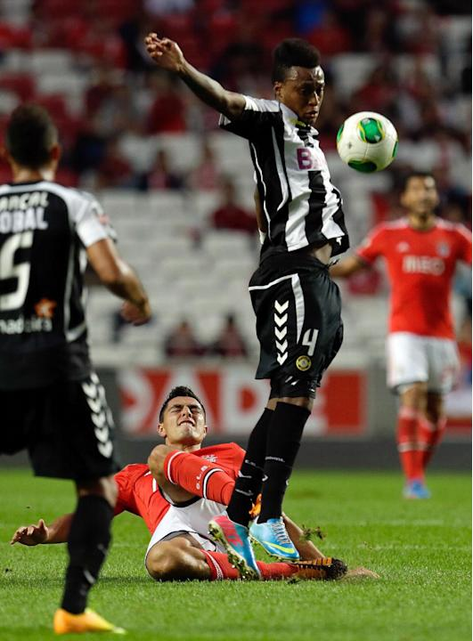 Benfica's Oscar Cardozo, from Paraguay, on the ground, fights for the ball with Nacional's Mexer, from Mozambique, during their Portuguese league soccer match, Sunday Oct. 27, 2013, at Benfica's Luz s