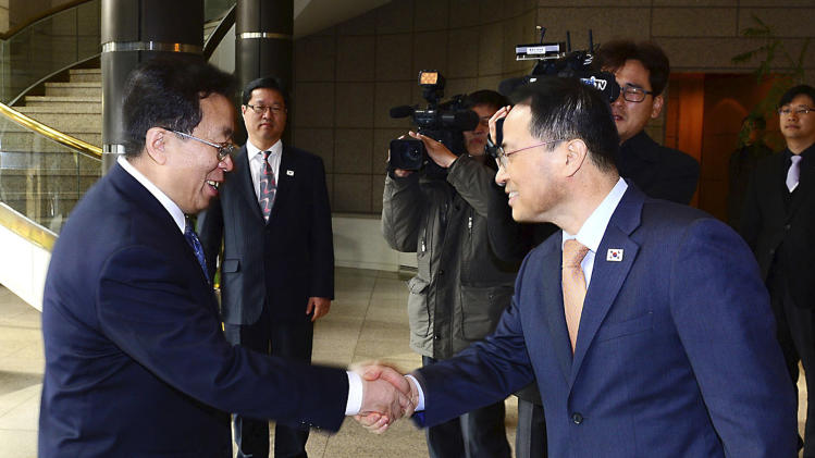 In this photo released by the South Korean Unification Ministry, South Korean chief delegate Kim Kyou-hyun, right, welcomes his North Korean counterpart Won Tong Yon upon arrival at the border village of Panumjom, South Korea, Friday, Feb. 14, 2014. The rival Koreas sat down Friday for a second round of talks this week at a border village as the North's calls for a delay of annual South Korea-U.S. military drills threaten plans for the resumption of emotional reunions of war-divided families. (AP Photo/South Korean Unification Ministry)