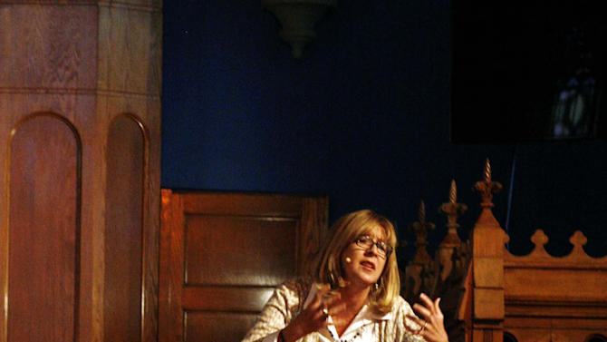 In this Nov. 2, 2014 photo, the Rev. Laura Truax preaches at a morning service at Lasalle Street Church in Chicago. In September, members and regulars at the church each received $500 checks from the church with the instruction that they were to do what they felt called to do with the money, which represented 10 percent of the profit from the sale of some land the church co-owned. (AP Photo/Martha Irvine)