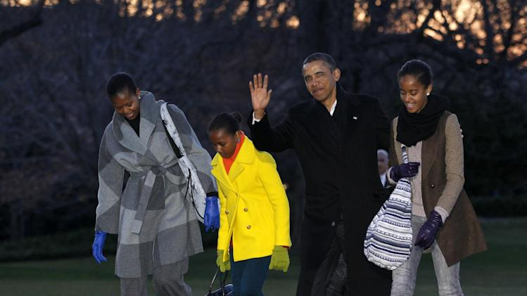 President Barack Obama, first lady Michelle Obama and their daughters Sasha and Malia arrive on the South Lawn of the White House, Tuesday, Jan. 3, 2012, in Washington. The first family was returning from their family vacation to Hawaii. (AP Photo/Haraz N. Ghanbari)