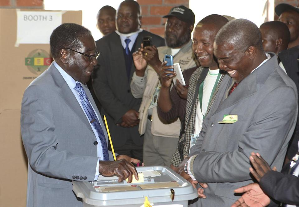Zimbabwean President Robert Mugabe, left, casts his vote in Harare, Wednesday, July, 31, 2013 Zimbabweans voted Wednesday in the elections that will determine the future of longtime President Robert Mugabe, who has denied allegations of vote-rigging despite concerns about the credibility of the polls. (AP Photo/Tsvangirayi Mukwazhi)