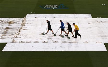 Groundsmen push water off covers on pitch during rain delay on final day of second cricket test between England and New Zealand in Wellington