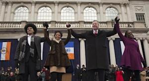 New York City Mayor Bill de Blasio and family raise their arms after his formal inauguration ceremony on the steps of City Hall in New York on January 1, 2014. REUTERS/Adrees Latif