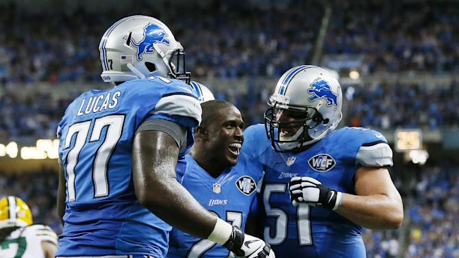 Detroit Lions running back Reggie Bush (21) is congratulated by teammates tackle Cornelius Lucas (77) and center Dominic Raiola (51) after his 26-yard rushing touchdown during the second half of an NFL football game against the Green Bay Packers in Detroit, Sunday, Sept. 21, 2014