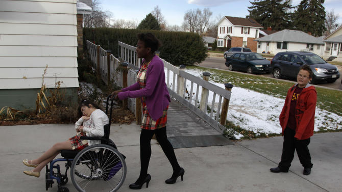In this Nov. 14, 2012 photo, three of the four disabled adopted children of Carrie Ann Lucas, who is also disabled, prepare to leave their home in Windsor, Colo., on a car outing. From left are: Heather, 22; Asiza, 17; and Anthony, 11. (AP Photo/Brennan Linsley)