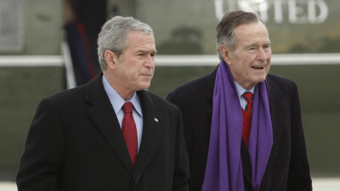 FILE - In this Dec. 26, 2008 file photo, President George W. Bush walks with his father, former President George H.W. Bush, at Andrews Air Force Base, Md. A criminal investigation is under way after a hacker apparently accessed private photos and emails sent between members of the Bush family, including both former presidents, the Houston Chronicle first reported Friday, Feb. 8, 2013. (AP Photo/Evan Vucci, File)