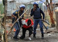 <p>South African police arrest a miner in Marikana on September 15, 2012 at Lonmin's platinum mine. A security crackdown on protesting miners in South Africa's restive platinum belt, where 45 people have died in a monthlong wildcat strike, appeared to bear fruit Monday as Lonmin, one of the biggest mines, re-opened.</p>