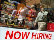"Pedestrians walk past a ""Now Hiring"" sign in the window of a GNC shop in Boston"