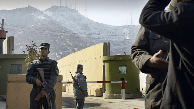 Afghan policemen stand guard outside of Kabul police headquarters, where a an American advisor was killed,  in Kabul, Afghanistan, Monday, Dec. 24, 2014. An Afghan policewoman killed an American adviser at the Kabul police headquarters on Monday, a senior Afghan police official said. (AP Photo/Musadeq Sadeq)
