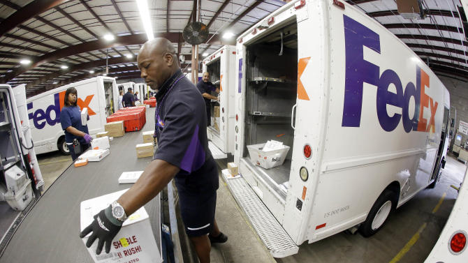 In this July 9, 2014 photo, Mitchell Rodgers loads packages into his delivery truck at the FedEx Express station in Nashville, Tenn. FedEx Corp., on Wednesday, Sept. 17, 2014, reported profit of $606 million in its fiscal first quarter. (AP Photo/Mark Humphrey)