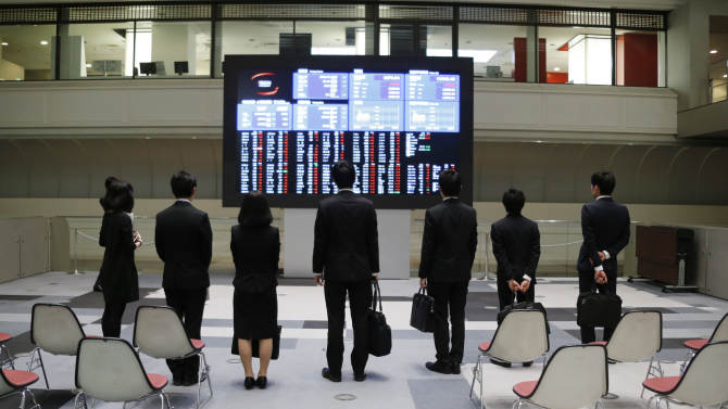 Visitors look at the stock prices on the monitors during a morning trading session at the Tokyo Stock Exchange  in Tokyo, Friday, April 5, 2013.  Japan's benchmark stock index hit 13,000 for the first time in more than four years Friday, a day after the country's central bank announced aggressive action to lift the economy out of an extended slump. (AP Photo/Koji Sasahara)