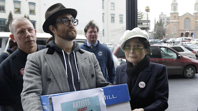 """Sean Lennon and Yoko Ono help deliver boxes of comments to the New York State Department of Environmental Conservation on its proposed natural gas drilling regulations on Friday, Jan. 11, 2013, in Albany, N.Y. Environmental, health and community groups opposed to shale gas drilling and hydraulic fracturing, or """"fracking,"""" say they collected more than 200,000 comments during an intense 30-day effort featuring online coaching and comment-writing workshops at churches, community centers, food co-ops, coffee shops and holiday house parties from New York City to Buffalo. (AP Photo/Mike Groll)"""