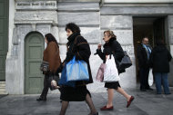 <p>               Athenians walk past a central Athens branch of  National Bank of Greece, the country's largest lender, Tuesday, Dec. 11, 2012. Greece was expected to announce later Tuesday the results of a bond buyback hoped to cut some 20 billion euros off the country's 340 billion euro debt load. Domestic lenders will contribute strongly in the European-funded buyback, which if successful will open the way for disbursement of a delayed international rescue loan payment. (AP Photo/Petros Giannakouris)