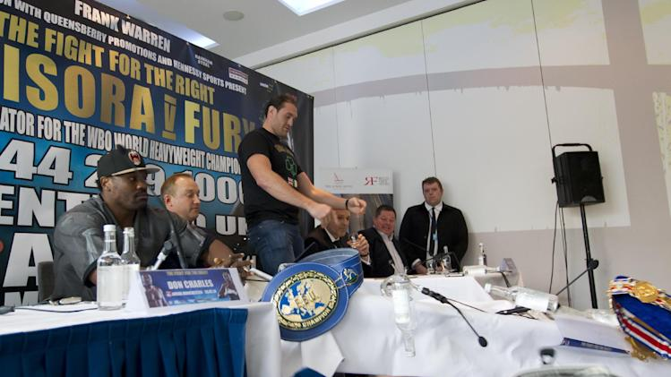 Boxer Tyson Fury, centre, upturns a table before walking out of a press conference with Dereck Chisora, left, to publicise their forthcoming a world title eliminator fight, Manchester, England, Thursday March 20, 2014. The fight will take place on 26 July in Manchester with the winner possibly going on to challenge IBF, WBA and WBO heavyweight champion Wladimir Klitschko. (AP Photo/Jon Super)