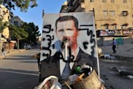 A vandalised poster of Syrian President Bashar al-Assad lies in a trash container in the northern city of Aleppo on July 24. Paris prosecutors opened a preliminary probe Thursday into the alleged involvement of French technology firm Qosmos in supplying Syria's regime with surveillance equipment, judicial sources said.