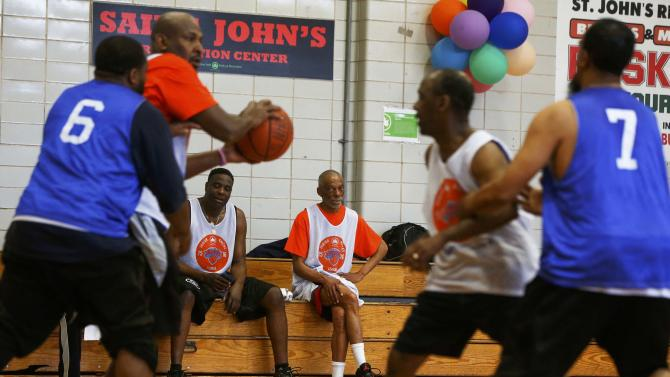 Men watch others compete in a basketball game during the Brooklyn Senior Games at the St. Johns Recreation Center in New York