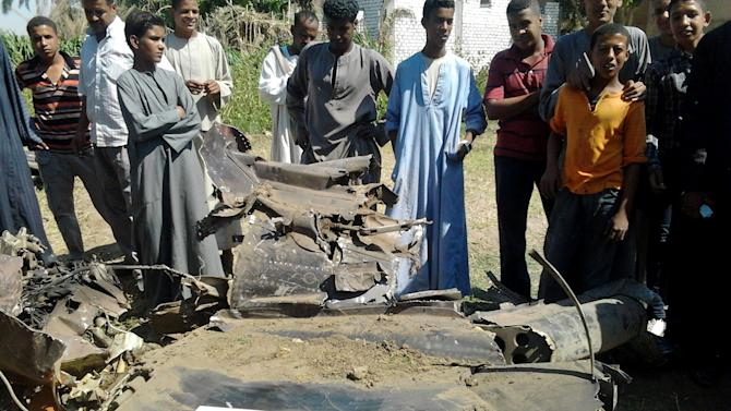 Egyptians gather around the remains of a Soviet-made MiG-21 fighter jet belonging to the Egyptian air force that crashed Sunday, while on a training mission near the southern ancient city of Luxor, which officials said killed a villager on the ground and injured several. The pilot bailed out and parachuted safely to the ground before the plane crashed in a rural area outside of Luxor, setting several houses on fire and damaging an elementary school. (AP Photo/Hagag Salama)