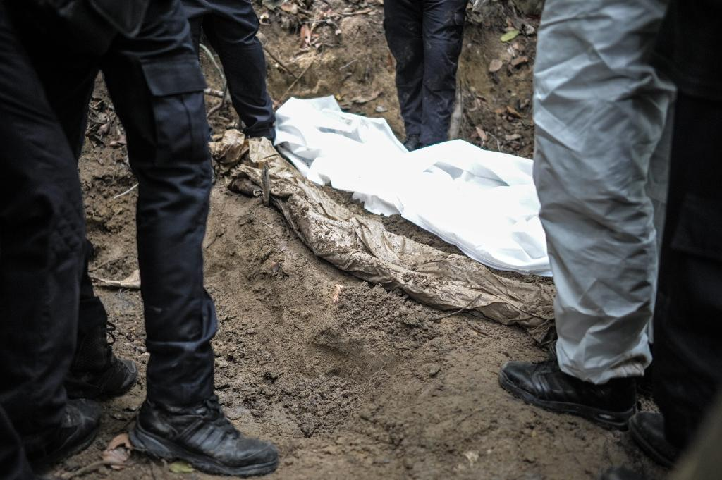 Bones and barbed wire as Malaysia exhumes migrant graves