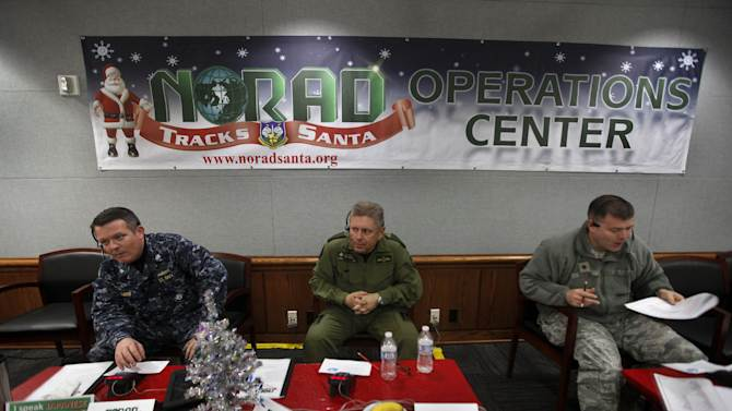 NORAD Deputy Commander Lt. General Alain Parent, center, of the Royal Canadian Air Force, who is the top ranking Canadian military officer stationed in the United States, takes phone calls from children asking where Santa is and when he will deliver presents to their house, during the annual NORAD Tracks Santa Operation, at the North American Aerospace Defense Command, or NORAD, at Peterson Air Force Base, in Colorado Springs, Colo., Monday Dec. 24, 2012. Also fielding calls are U.S. Navy Capt. Jeff Davis, left, and U.S. Air Force Maj. Chris Bendig. Over a thousand volunteers at NORAD handle more than 100,000 thousand phone calls from children around the world every Christmas Eve, with NORAD continually projecting Santa Claus' purported position delivering presents.  (AP Photo/Brennan Linsley)