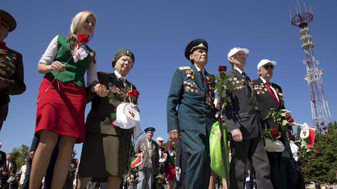 A woman accompanies World War Two veterans who attend a wreath-laying ceremony in Victory Square during celebrations marking Independence Day in Minsk