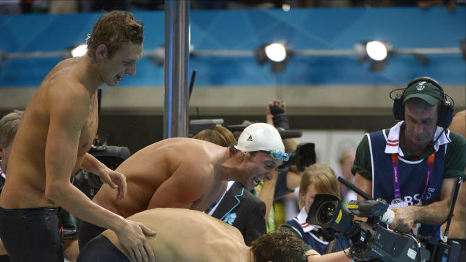 France's Clement Lefert, center, France's Amaury Leveaux, left, France's Fabien Gilot, back right, and France's Yannick Agnel celebrate as they win gold in the men's 4x100-meter freestyle relay final at the Aquatics Centre in the Olympic Park during the 2012 Summer Olympics in London, Sunday, July 29, 2012.(AP Photo/Mark J. Terrill)