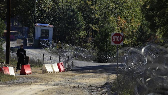 In this Thursday, Oct. 11, 2012, a private security guard stands amid coils of razor wire at the entrance to a gold mine complex in Skouries, in the Halkidiki peninsula in northern Greece. Mining company Hellas Gold expects the mine to be up and running by mid 2015 creating about 2000 jobs for the next five years. But while some see the gold mine seen as a savior _ as Greece enters a sixth year of recession amid record-high unemployment _ others revile it as an environmental catastrophe that will do little to help the economy.  (AP Photo/Nikolas Giakoumidis)