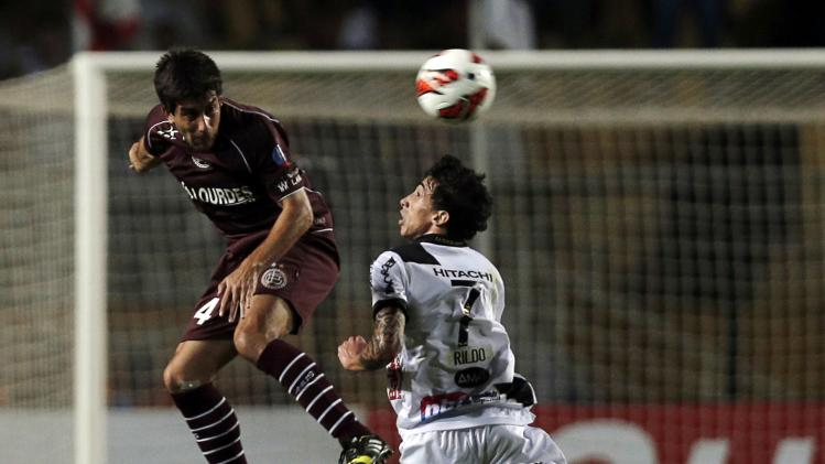 Araujo of Argentina's Lanus jumps for the ball with Rildo of Brazil's Ponte Preta during their Copa Sudamericana first leg final soccer match in Sao Paulo
