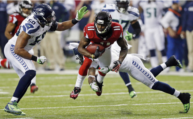 Atlanta Falcons wide receiver Julio Jones (11) works against Seattle Seahawks outside linebacker K.J. Wright (50) and free safety Earl Thomas (29) during the second half of an NFC divisional playoff N