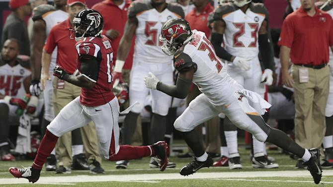 Atlanta Falcons wide receiver Devin Hester (17) runs by Tampa Bay Buccaneers free safety Keith Tandy (37) during the first half of an NFL football game, Thursday, Sept. 18, 2014, in Atlanta