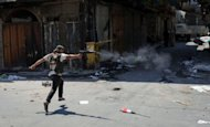 A Syrian rebel from the Free Syrian Army fires his rifle down a street towards government snipers in the Bab Al-Nasr district of the northern restive city of Aleppo