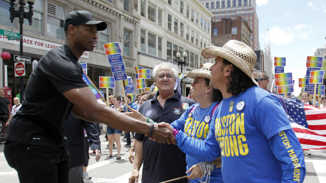 NBA veteran Jason Collins, left, the first active player in one of four major U.S. professional sports leagues to come out as gay, shakes hand with Boston Marathon hero Carlos Arredondo, as they both participated in Boston's gay pride parade, Saturday, June 8, 2013, in Boston. Looking on is former Congressman Barney Frank, second from left. (AP Photo/Mary Schwalm)