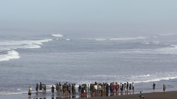 People gather on Muriwai Beach near Auckland, New Zealand, Thursday, Feb. 28, 2013, to say goodbye to Adam Strange. About 150 friends and family of Strange, 46, wrote messages to him in the sand and stepped into the water Thursday at a New Zealand beach to say goodbye after he was killed Wednesday by a large shark. (AP Photo/New Zealand Herald, Brett Phibbs) New Zealand Out, Australia Out