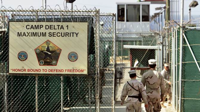FILE - In this June 27, 2006 file photo, reviewed by a U.S. Department of Defense official, U.S. military guards walk within Camp Delta military-run prison, at the Guantanamo Bay U.S. Naval Base, Cuba. President Barack Obama is pushing to overcome obstacles to closing the Guantanamo Bay prison, an elusive goal which has frustrated him since he took office. That is setting the White House on a collision course with Congress in its bid to loosen restrictions for moving out detainees. (AP Photo/Brennan Linsley, File)