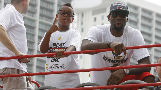 Miami Heat's LeBron James, right, and his son, Lebron Jr., look out from a doubledecker bus during a parade in celebration of winning the NBA Finals basketball championship against the Oklahoma City Thunder, Monday, June 25, 2012, in Miami. (AP Photo/Lynne Sladky)