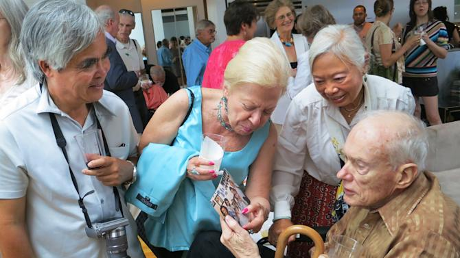 In this Aug. 11, 2012 photo, former Associated Press Saigon bureau chief Malcolm Browne, right, and his wife Lelieu, second from right, look at a photo shown to him by Edith M. Lederer showing her in Vietnam where she too served as an AP correspondent along with with AP photographer Nick Ut, left, at a memorial tribute in New York to former AP Vietnam staffers Horst Faas and George Esper. Browne died Monday, Aug 27, 2012, in a New Hampshire hospital at age 81. He was acclaimed for his trenchant reporting of the Vietnam War and a photo of a Buddhist monk's suicide by fire that shocked the Kennedy White House into a critical policy re-evaluation. (AP Photo/Valerie Komor)