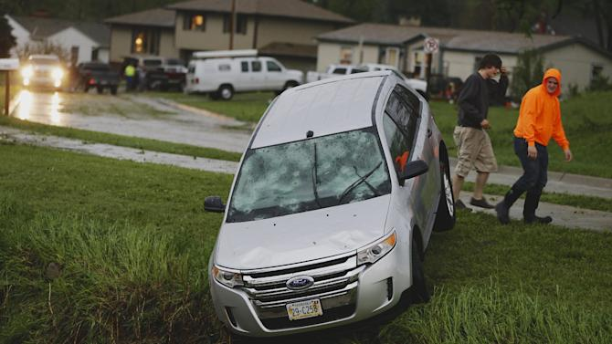 A car with it's windows smashed from hail hangs over a creek following a severe thunderstorm in Blair, Neb., Tuesday, June 3, 2014. Severe weather packing large hail and heavy rain rolled into Nebraska and Iowa on Tuesday as potentially dangerous storms targeted a swath of the Midwest, including states where voters were casting ballots in primary elections. (AP Photo/Nati Harnik)