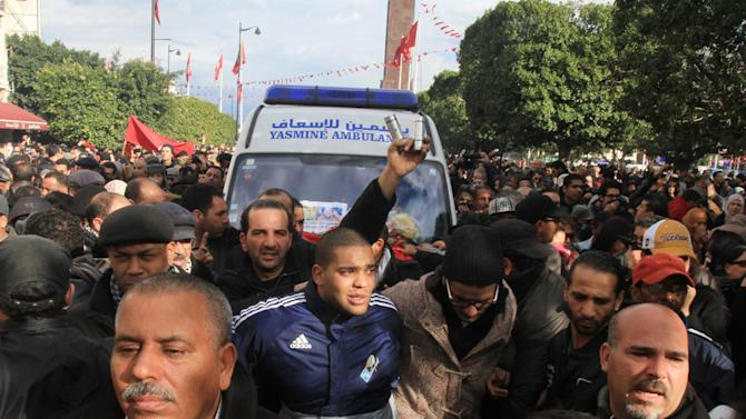 Protesters surround the ambulance carrying the body of Chokri Belaid after he was shot to death in Tunis, Wednesday, Feb. 6, 2013. The Tunisian opposition leader critical of the Islamist-led government and violence by radical Muslims was shot to death Wednesday — the first political assassination in post-revolutionary Tunisia. The killing is likely to heighten tensions in the North African nation whose path from dictatorship to democracy so far has been seen as a model for the Arab world. (AP Photo/Amine Landoulsi)