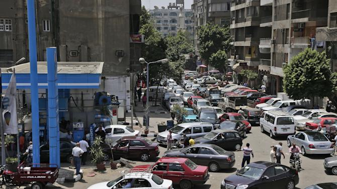 Egyptian drivers wait in long queues outside a gasoline station, in Cairo, Egypt, Wednesday, June 26, 2013. Fuel shortages have caused long lines for months, but Egypt's Supply Minister Bassem Ouda told a news conference that the latest fuel shortage will end in a matter of days. Authorities blame the shortage on a technicalproblem at a majorpetrol depoton the outskirts of Cairo. (AP Photo/Hassan Ammar)