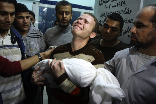 Jihad Masharawi weeps while he holds the body of his 11-month old son Ahmad, at Shifa hospital following an Israeli air strike on their family house, in Gaza City, Wednesday, Nov. 14, 2012. The Israel