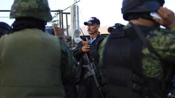 A member of the Community Police from the FUSDEG argues with a group of soldiers over their presence in the village, at an entry to Petaquillas